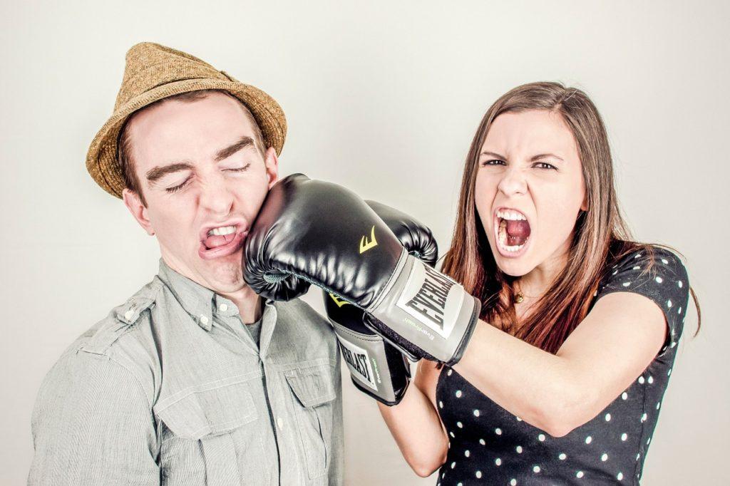 Dívka zasazuje ránu boxerskou rukavicí muži